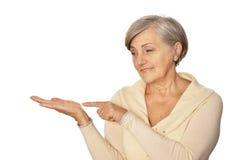 Senior lady pointing. On a white background Stock Photos