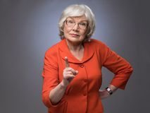 Senior lady points finger up. On gray background with copy space stock image