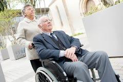 Senior lady pushing husband in wheelchair. Senior lady pushing her husband in his wheelchair Royalty Free Stock Images