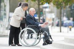 Senior lady pushing husband in wheelchair. Senior lady pushing her husband in his wheelchair Royalty Free Stock Photos