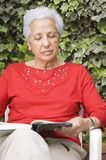 Senior lady reading. Mature woman reading a book in her garden Royalty Free Stock Photography