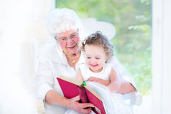 Senior lady reading book to her granddaughter Royalty Free Stock Images