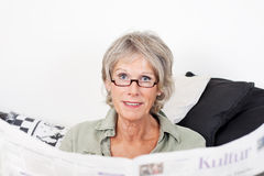 Senior lady reading her newspaper at home. Relaxing on a couch and peering over the top at the viewer Stock Photo