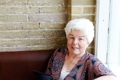 Senior lady reading tablet Royalty Free Stock Photos