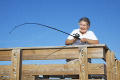 Senior Lady Reels in Fish Stock Image