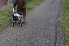 senior lady with rollator on a bikeway royalty free stock photography