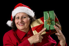Senior Lady with Santa Cap Points at Wrapped Gifts. Elderly lady with Santa Claus cap and red velvet coat is pointing with her right index finger at two wrapped Royalty Free Stock Photography
