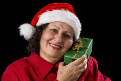 Senior Lady with Santa Claus Hat and Wrapped Gift. Smiling old lady with a Santa Claus cap and a red coat is holding a green wrapped Christmas present with her Royalty Free Stock Image