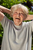 Senior lady with a sense of humour. Senior lady with a good sense of humour having a hearty laugh as she enjoys the sunshine outdoors in her garden on a summer royalty free stock photos