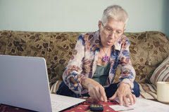 Senior lady shocked with her bills. Elderly woman outraged with the bills she received stock image
