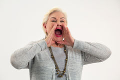 Senior lady shouting. Woman holding hands near mouth Stock Photography