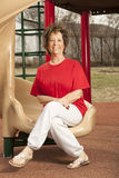 Senior lady sits on the slide. At the park where she can see the grand kids royalty free stock image