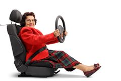 Senior lady sitting in a car seat and driving. Isolated on white background stock images