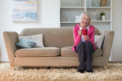 Senior lady sitting at home. On her sofa in the living room. She is smiling at the camera and holding a cup of tea Stock Photography