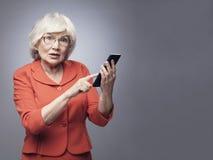 Senior lady with smartphone Royalty Free Stock Image