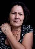 Senior lady suffering from shoulder pain. Portrait of a senior lady suffering from shoulder pain on a black background Royalty Free Stock Image