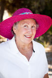Senior Lady in Sun Hat. Outdoor portrait of a beautiful senior woman in a pink sun hat royalty free stock images