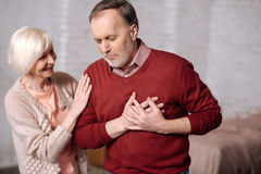 Senior lady supporting husband with heartache. So sudden. Portrait of aged men with heartache standing and touching his heart area while his wife supporting him Royalty Free Stock Images