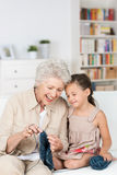 Senior lady teaching her granddaughter to knit royalty free stock images