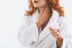 Senior lady treating her skin with moisturizer Stock Image