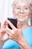 Senior lady using cellular phone application Royalty Free Stock Photo