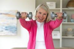 Senior lady using dumbbells. Stock Images