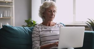 Senior lady using laptop typing on computer sitting on sofa