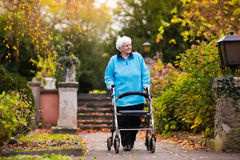 Senior lady with a walker in autumn park royalty free stock photography