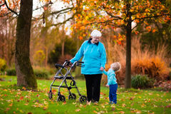 Senior lady with walker enjoying family visit. Happy senior lady with a walker or wheel chair and children. Grandmother and kids enjoying a walk in the park Stock Photo