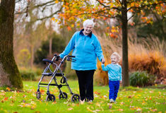 Senior lady with walker enjoying family visit. Happy senior lady with a walker or wheel chair and children. Grandmother and kids enjoying a walk in the park Royalty Free Stock Photo