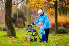 Senior lady with walker enjoying family visit. Happy senior lady with a walker or wheel chair and children. Grandmother and kids enjoying a walk in the park Stock Image