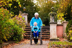 Senior lady with walker enjoying family visit. Happy senior lady with a walker or wheel chair and children. Grandmother and kids enjoying a walk in the park Royalty Free Stock Photos