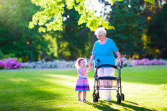 Senior lady with a walker and little girl in a park. Happy senior lady with a walker or wheel chair and a little toddler girl, grandmother and granddaughter stock image