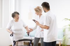 Senior lady with walker during physiotherapy with professional female doctor and male nurse stock images