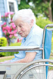 Senior lady in wheel chair in front of house Royalty Free Stock Photos
