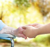 Senior lady in wheel chair holding hands with young caretaker Royalty Free Stock Image