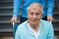 Senior lady in wheelchair with caretaker. In front of staircase royalty free stock photo
