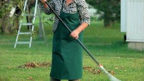 Senior lady working with rake. stock video footage