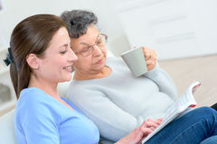 Senior lady and younger lady looking at book together Royalty Free Stock Photography