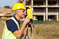 Senior land surveyor. Working with theodolite at construction site stock photography