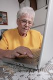 Senior with a laptop. Senior woman typing a message on a laptop Stock Image