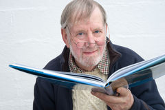 Senior with large book. A close up image of a Senior reading a high quality glossy picture book Stock Image