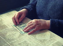 Senior latino female with small amount of money, toned image, colorized, selective focus, very shallow dof Stock Photos