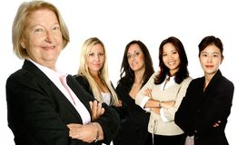 Senior lead with diverse team. Mature female caucasian  leading a team of business women from diverse background made up of a caucasian, a mediterranean, an Royalty Free Stock Photo