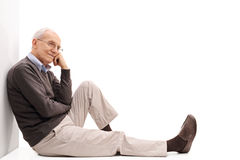 Senior leaning against a wall and thinking. Studio shot of a joyful senior leaning against a wall and thinking seated on the floor isolated on white background stock photography