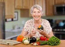 Senior learner of nutrition school online. Smiling senior woman is sitting at the table with fresh vegetables. She is a learner of nutrition school online stock photos