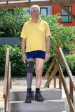 Senior leg amputee standing on staircase of training course for practicing Royalty Free Stock Image
