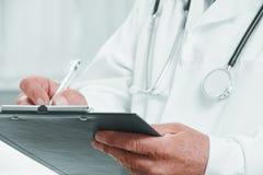 Senior lekarka pisze książeczkach zdrowia zdjęcie royalty free