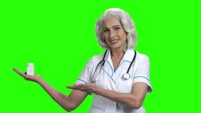 Senior lekarka przedstawia pigułki na zieleń ekranie zbiory
