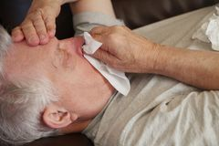 Senior lies down with flu symptoms Royalty Free Stock Photography